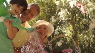 Senior couple in garden with grandson watering plants.