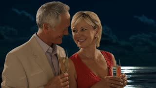 senior couple in moonlight toasting camera with champagne