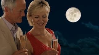 senior couple in moonlight toasting each other with champagne