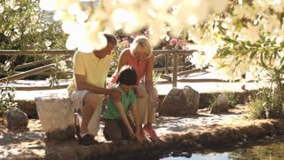 Senior couple in park with grandson playing with water.