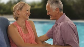 senior couple relaxing by pool