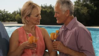 senior couple relaxing by poolside with drinks