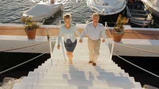 senior couple running up steps towards camera by marina in sunset