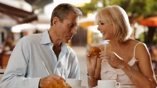 Senior couple sitting in cafe eating croissant and laughing together.