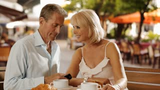 Senior couple sitting in cafe laughing together and taking photograph.
