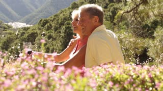 Senior couple sitting in countryside enjoying picnic.