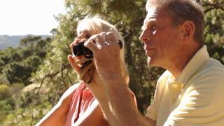 Senior couple sitting in countryside enjoying views with binoculars.