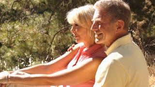 Senior couple sitting in countryside enjoying views.
