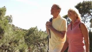 Senior couple walking in countryside.