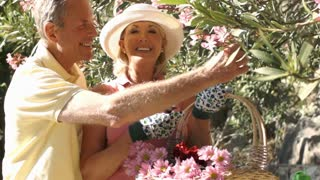 Senior couple with flower basket gardening.