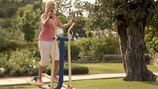 Senior woman using exercise machine in park.