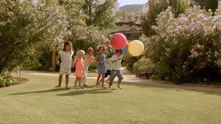 Six children running with balloons in park