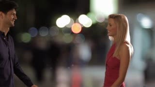 Slow motion couple embracing beside a water fountain at night.
