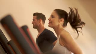 Slow motion dolly shot of couple on treadmill at gym.