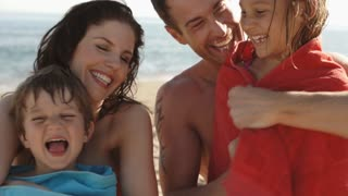 Slow motion family on beach, parents wrapping children in towels.