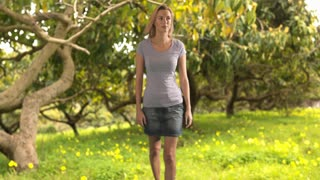 Slow motion of a woman walking in a park.