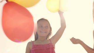 Slow motion of children playing on beach holding balloons.
