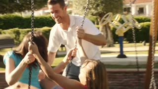 Slow motion of family in park father pushing mother and daughter on swing.