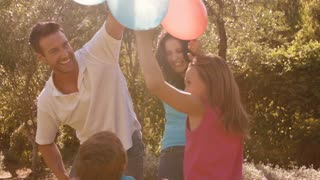 Slow motion of family in park playing with balloons.