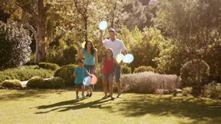 Slow motion of family in park running with balloons.