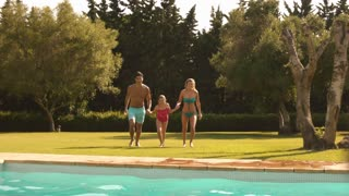 Slow motion of family jumping in pool.