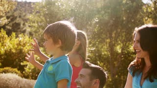 Slow motion of family playing with bubbles in park