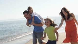 Slow motion of family running along beach and parents carrying children.
