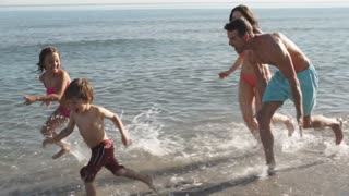 Slow motion of family running along beach at edge of sea.