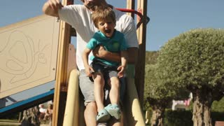 Slow motion of father and son on slide in park.