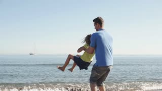 Slow motion of father spinning daughter around on beach.