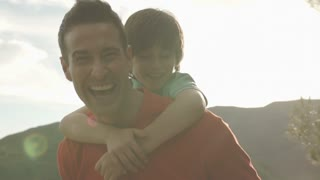 Slow motion of father with son on back playing in countryside.