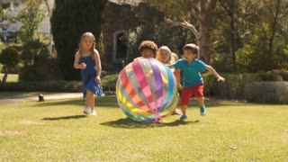 Slow motion of five children pushing beach ball towards camera in park.