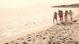 Slow motion of five children running on beach