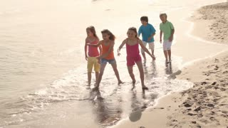 Slow motion of five children running on beach.