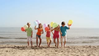 Slow motion of five children running towards camera on beach holding balloons.