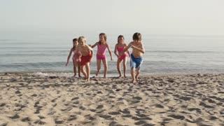 Slow motion of five children running towards camera on beach.