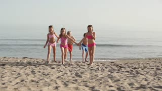 Slow motion of five children running towards camera on beach.