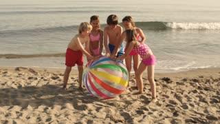 Slow motion of five children running towards camera pushing beach ball on beach.