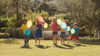 Slow motion of five children running towards camera with balloons.