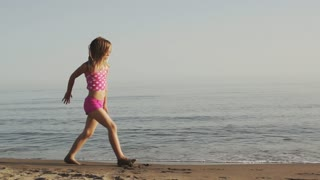 Slow motion of girl doing cartwheels on beach.