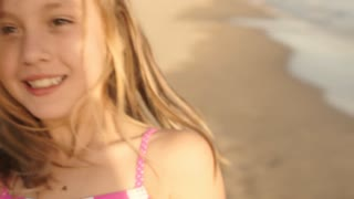 Slow motion of girl twirling around on beach.