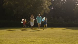 Slow motion of grandchildren and grandparents running to camera in garden holding balloons.