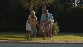 Slow motion of grandchildren jumping into swimming pool in garden.