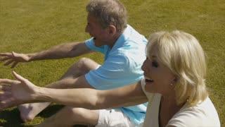 Slow motion of grandchildren running to grandparents and hugging on grass in garden.