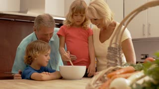 Slow motion of grandparents and grandchildren in kitchen mixing flour in bowl.