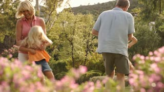 Slow motion of grandparents and grandchildren twirling around in park.