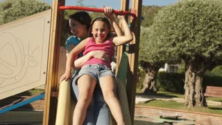 Slow motion of mother and daughter on slide in park