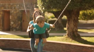 Slow motion of mother pushing son on swing in park.