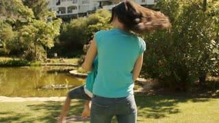 Slow motion of mother twirling with her son in a park.