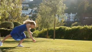 Slow motion of one child doing cartwheels in park.